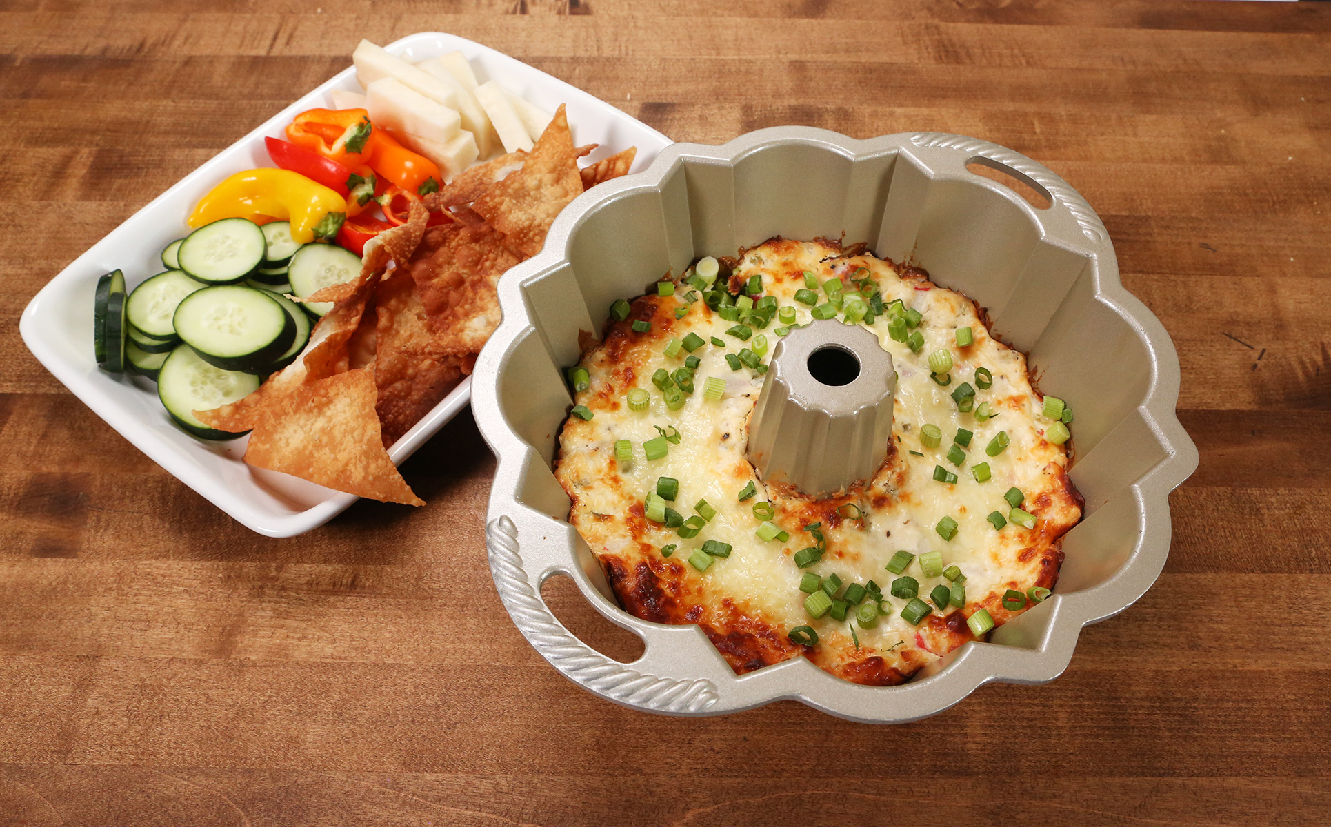 baked dish in fluted tube pan next to plate of chips and veggies