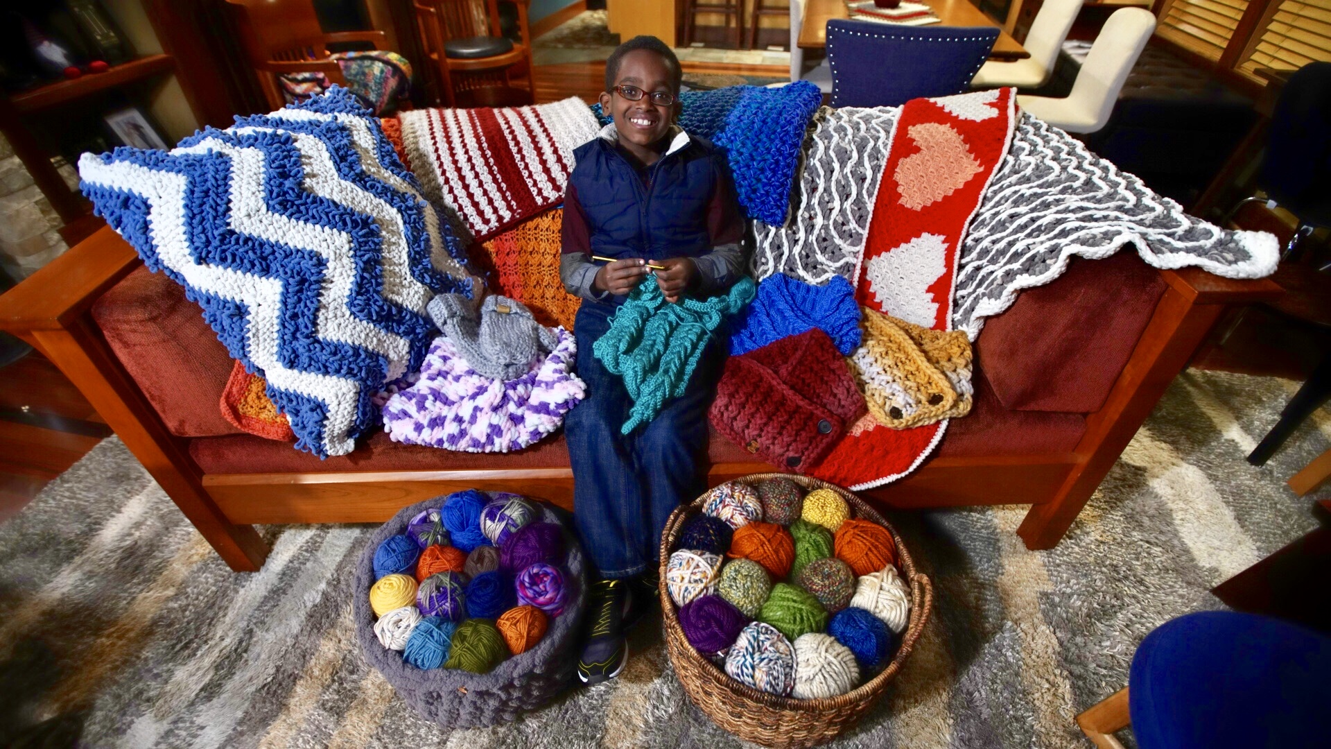 Boy sitting on a couch surrounded by crocheted things