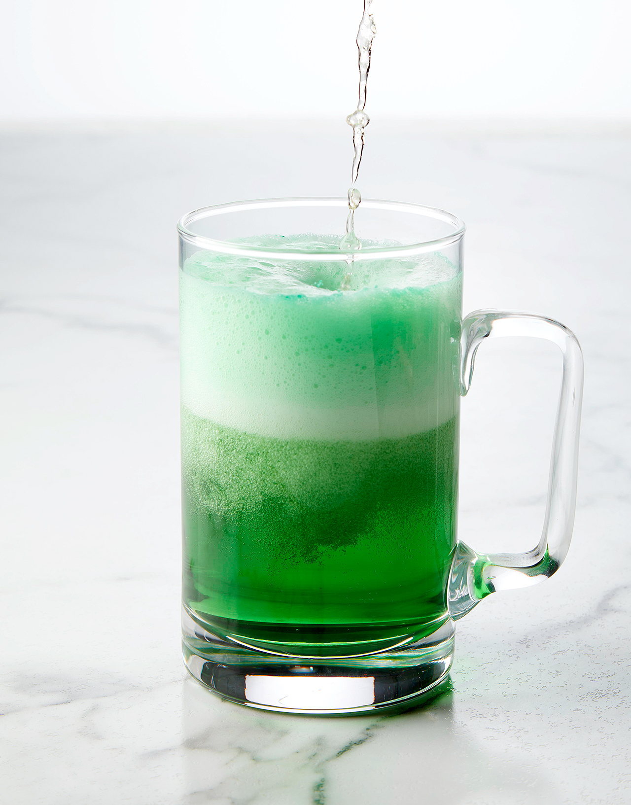 pouring beer into glass with food coloring