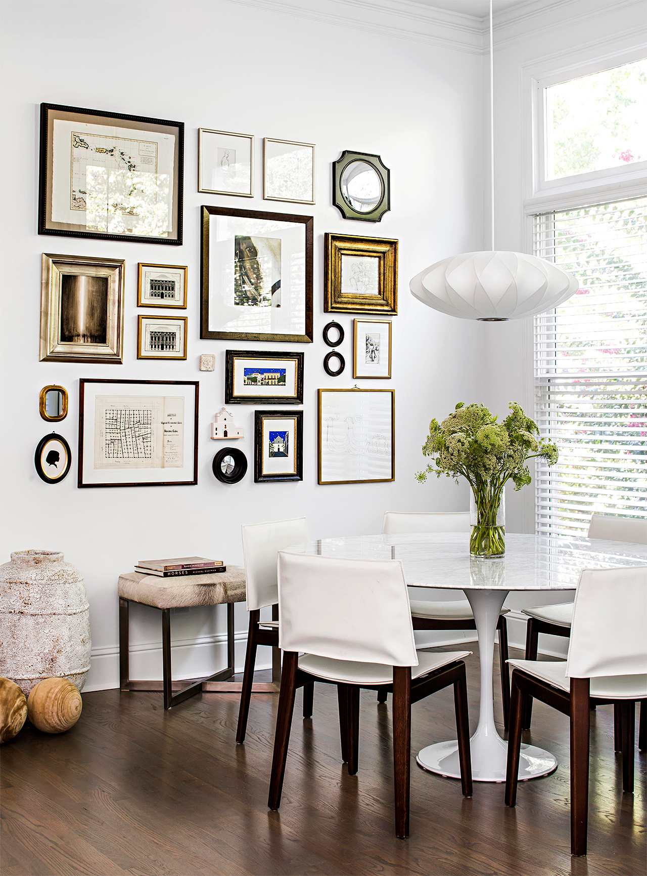 gallery wall in dining room with warm wood tones