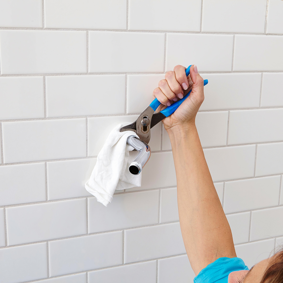 using wrench on showerhead pipe white tiled wall
