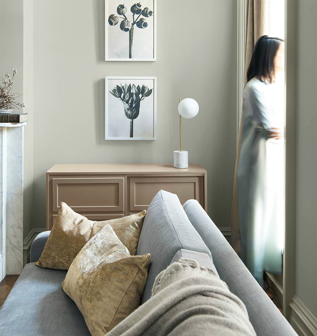 soft paint colors in living room with artwork chest of drawers and sofa with woman looking out window