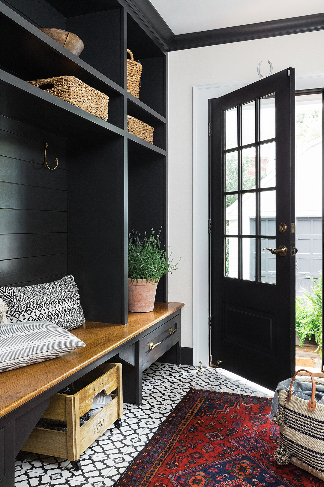 dark painted mudroom storage and door with patterned rug and wicker baskets