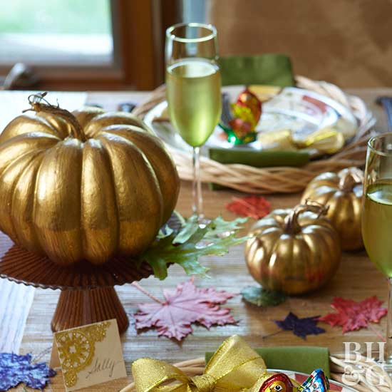 gold pumpkins as centerpiece on table set for Thanksgiving