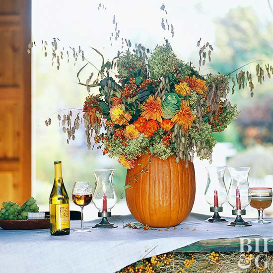 pumpkin centerpiece with orange flowers berries and candles