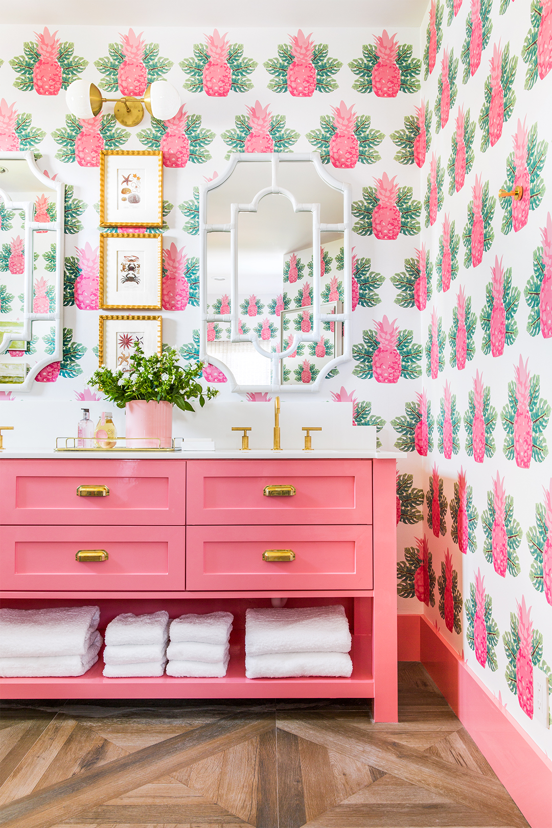 bathroom with pink pineapple wallpaper and pink his and her sinks