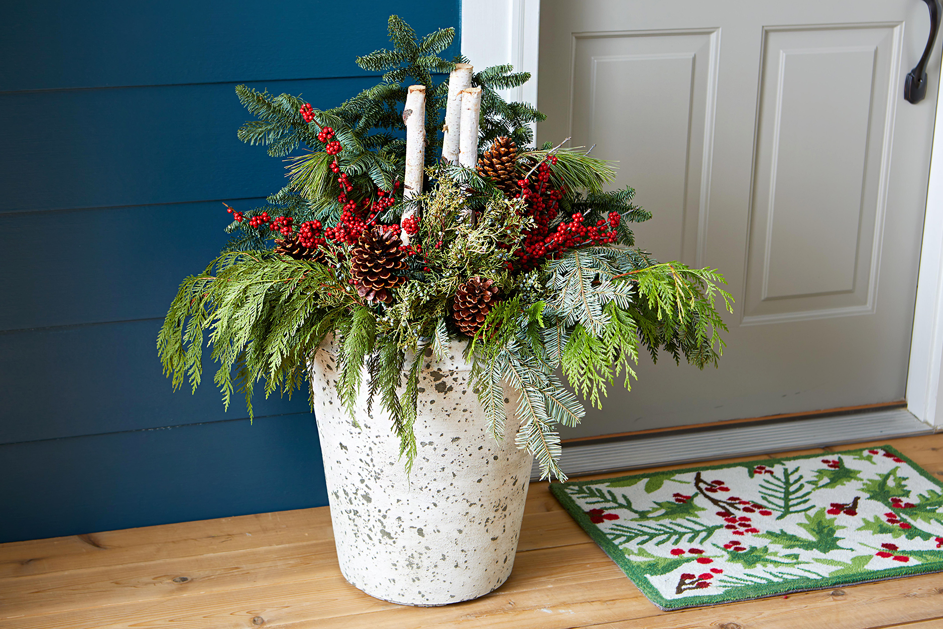 ceramic planter on porch with holiday greenery
