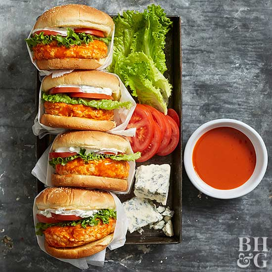four buffalo chicken burgers on a tray with lettuce tomato and blue cheese