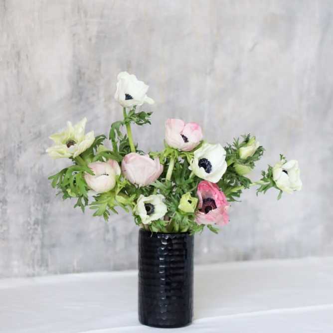 15 anemone stems with different colored blooms in black cylindrical vase