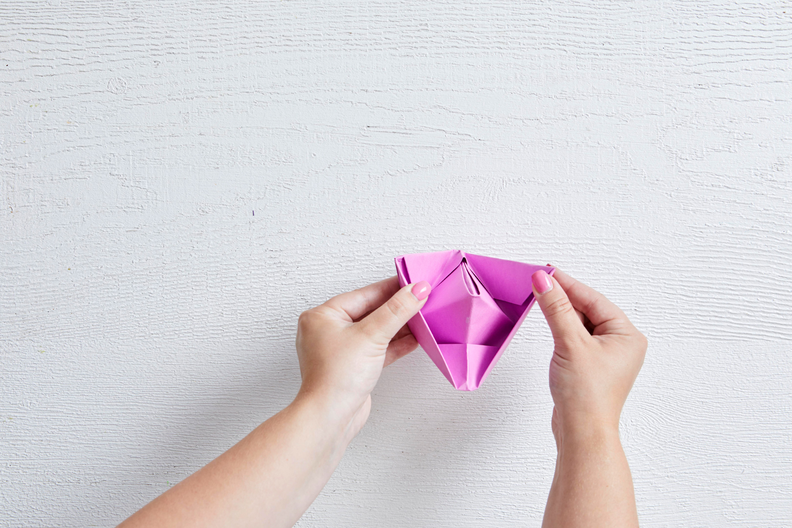 creating last folds of pink appetizer paper boats