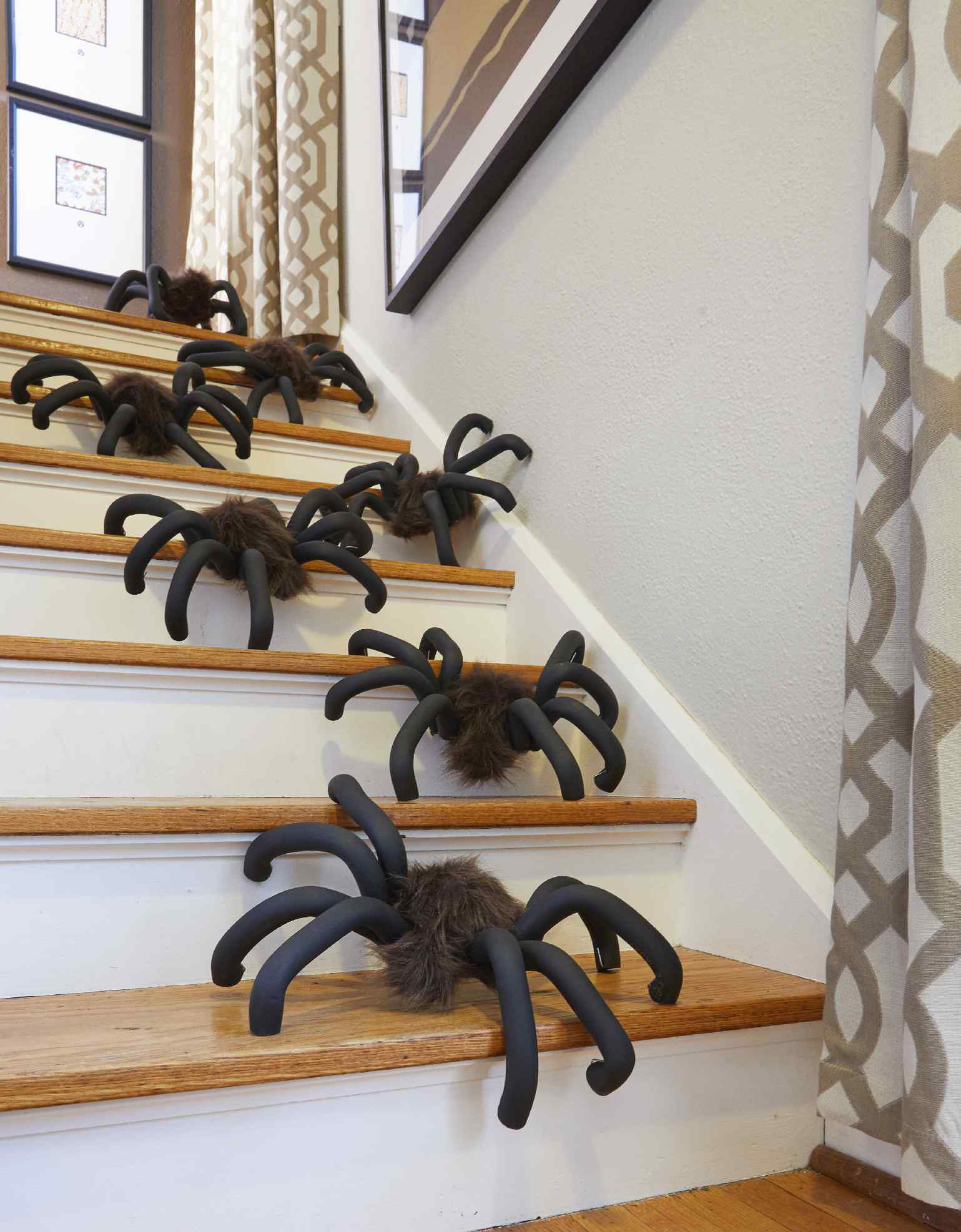 Large DIY fuzzy spiders climbing in a line down stairs