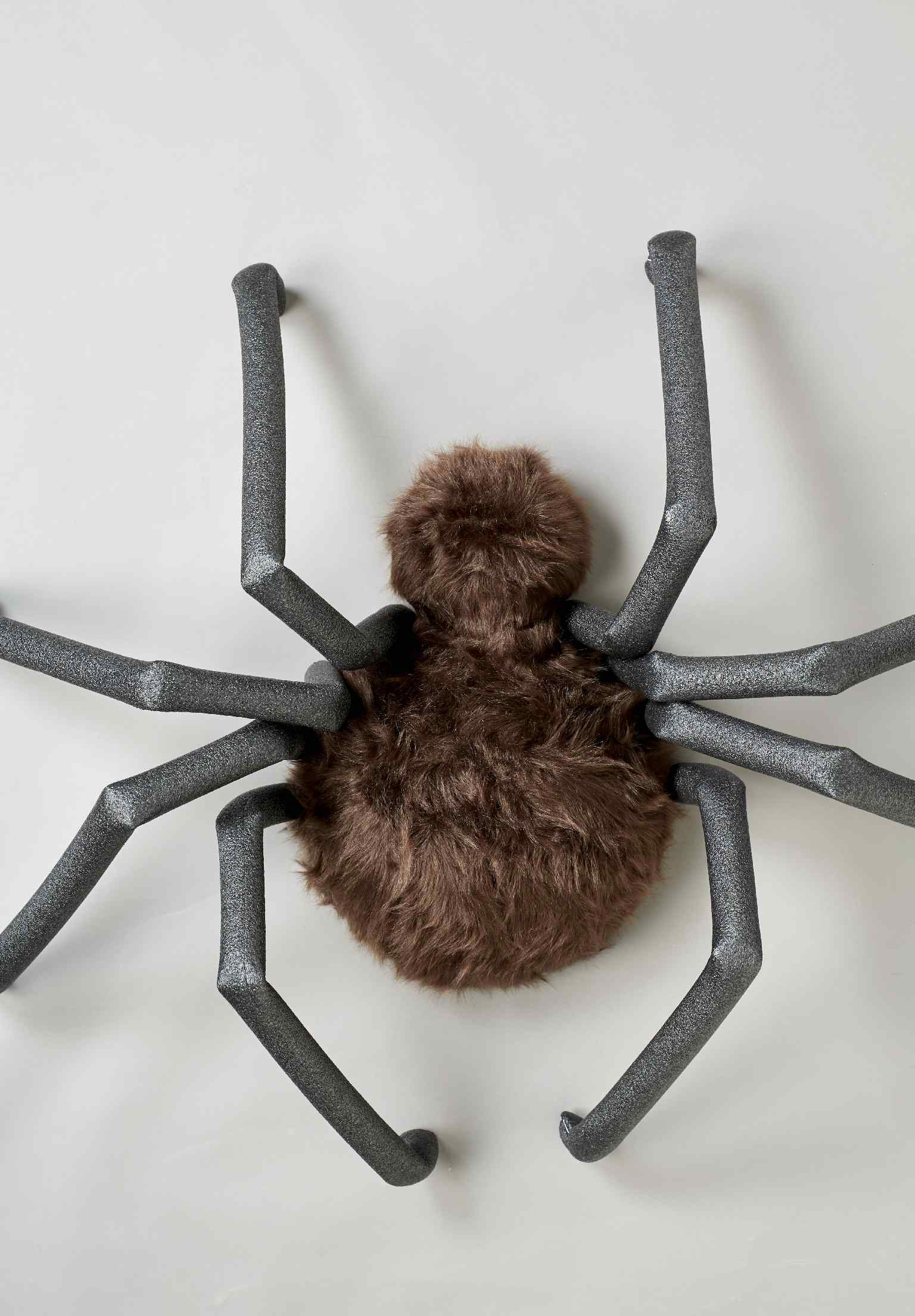 Large spider body covered in brown faux fur with black foam tubes folded to look like legs