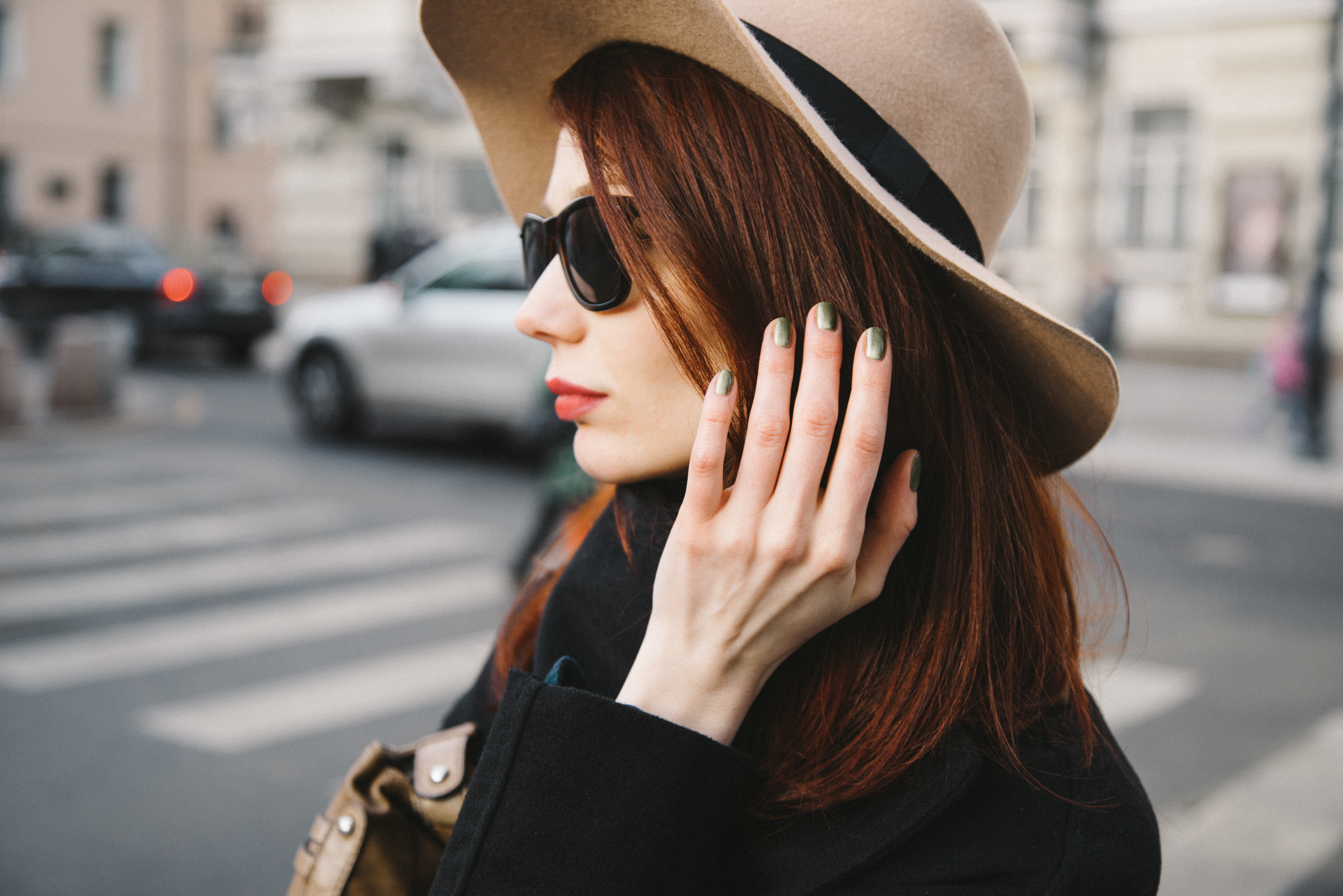 Woman wearing hat holding hair back with painted nails