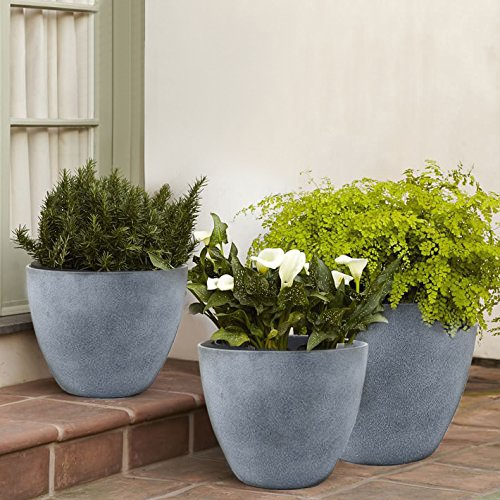 Three gray resin plants filled with greenery plants on a brick patio