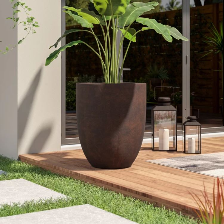 Large planter on wood patio with dark brown, rusted finish and a tropical plant with big leaves inside