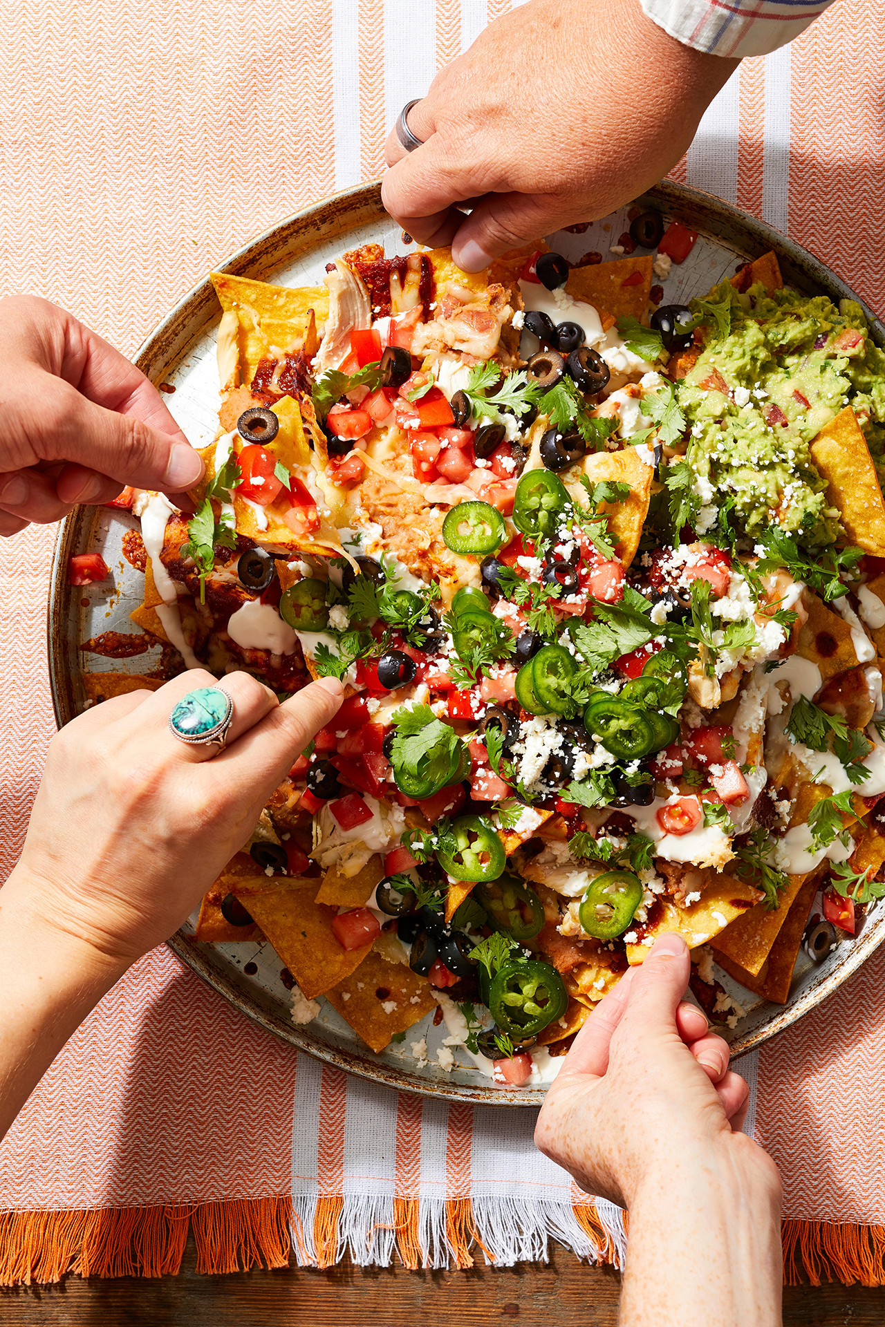 Guests grabbing chips from Mexican Party Nachos