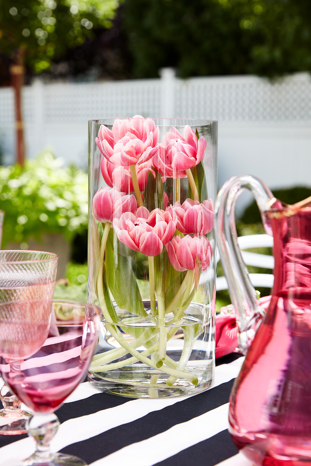 tulips in glass vase on striped table