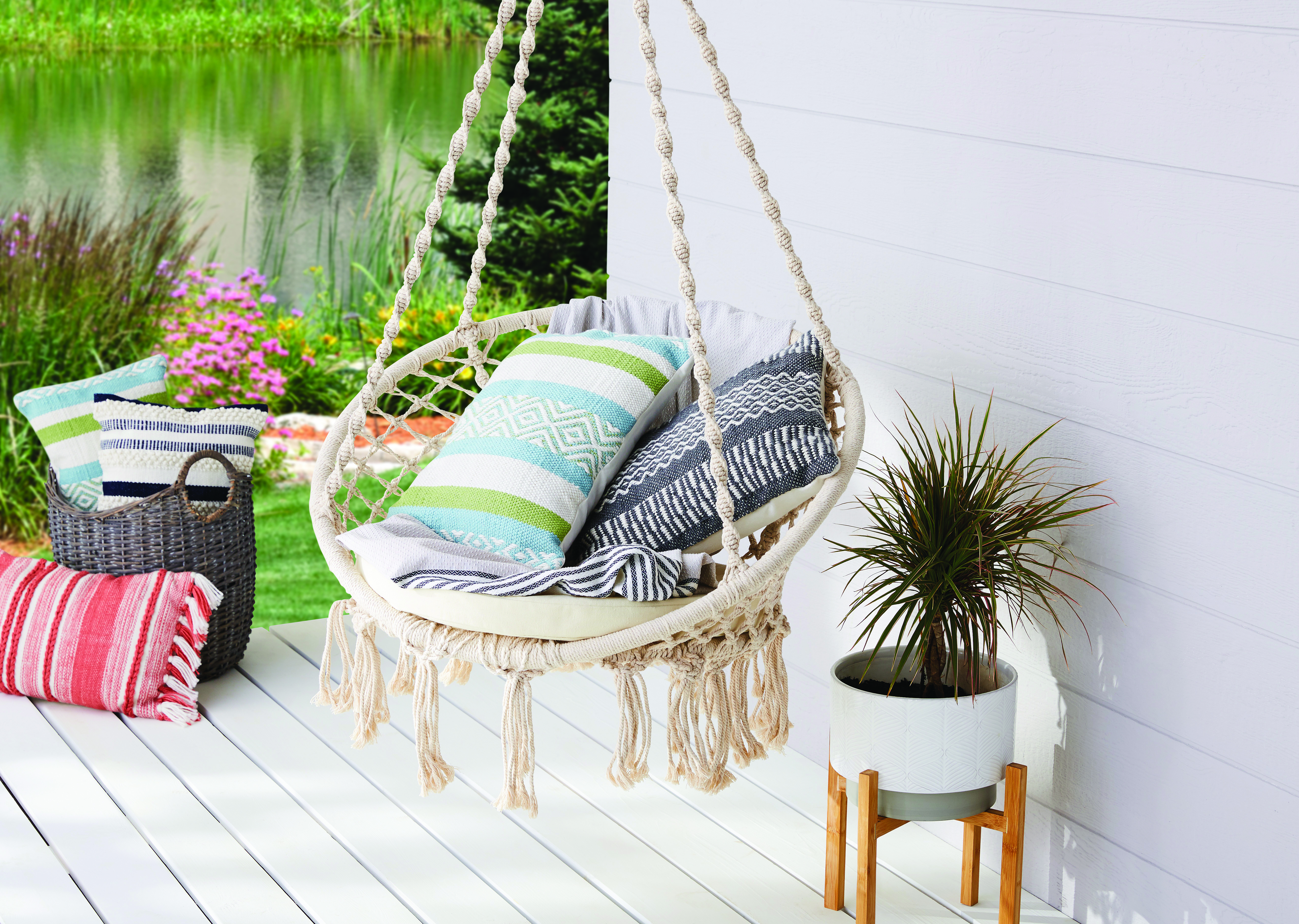 white hammock with blue pillows hanging on a white front porch