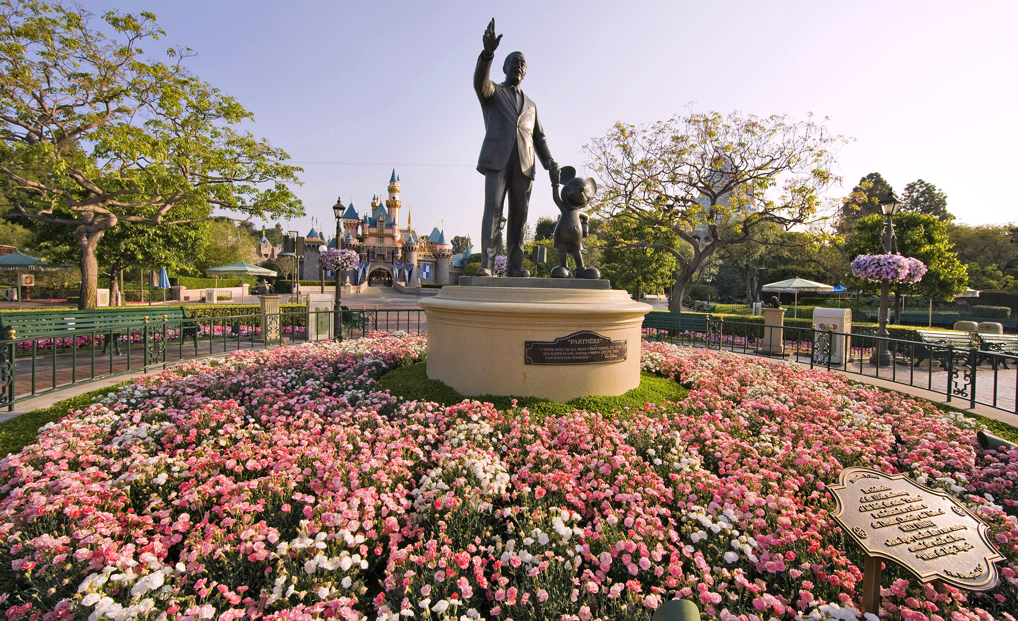 Partners bronze statue of Walt Disney and Mickey Mouse surrounded by pink at white flowers at Disneyland