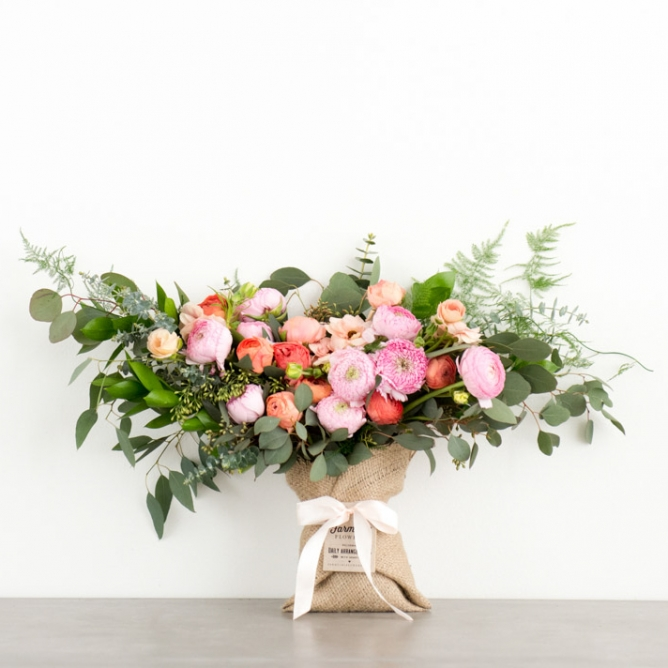 Bouquet with pink and orange ranunculus flowers, stems of eucalyptus, wrapped in burlap with an ivory bow
