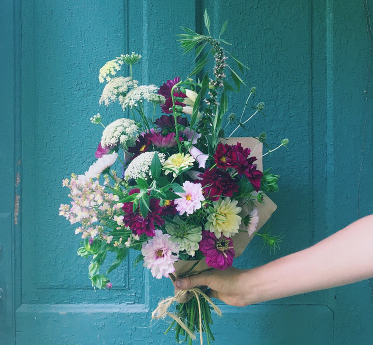 Hand holding a bouquet of Queen Anne's Lace, Zinnia, and other wildflowers against teal door
