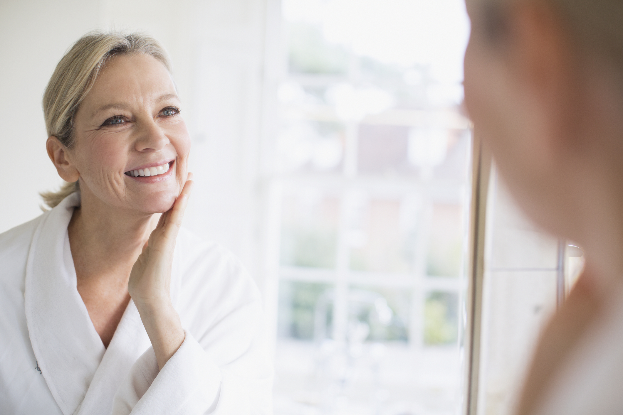 older woman looking into mirror at skin