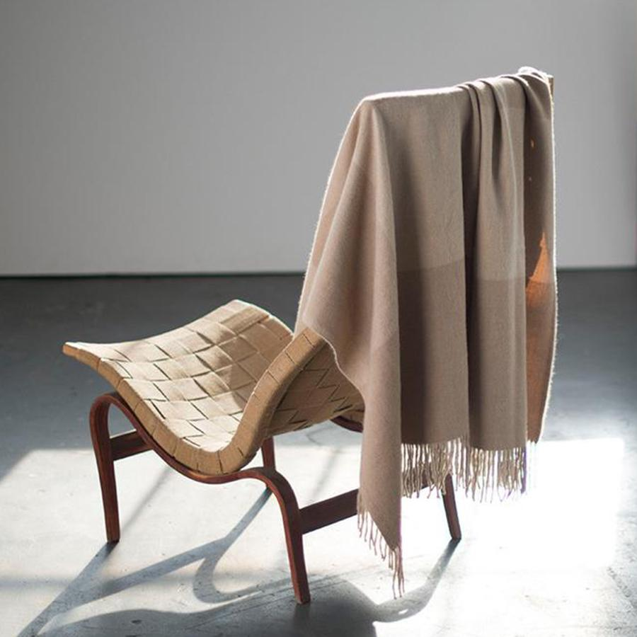 taupe throw blanket over back of a wood chair