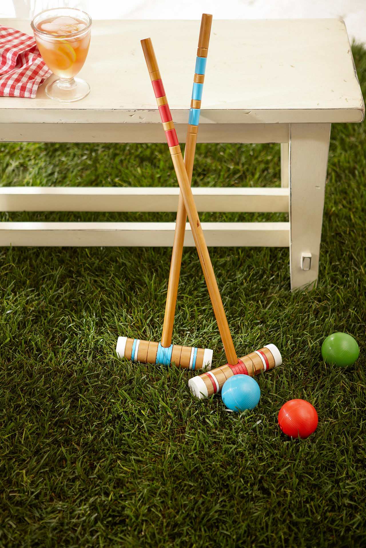 croquet mallets leaning against white bench with croquet balls on ground