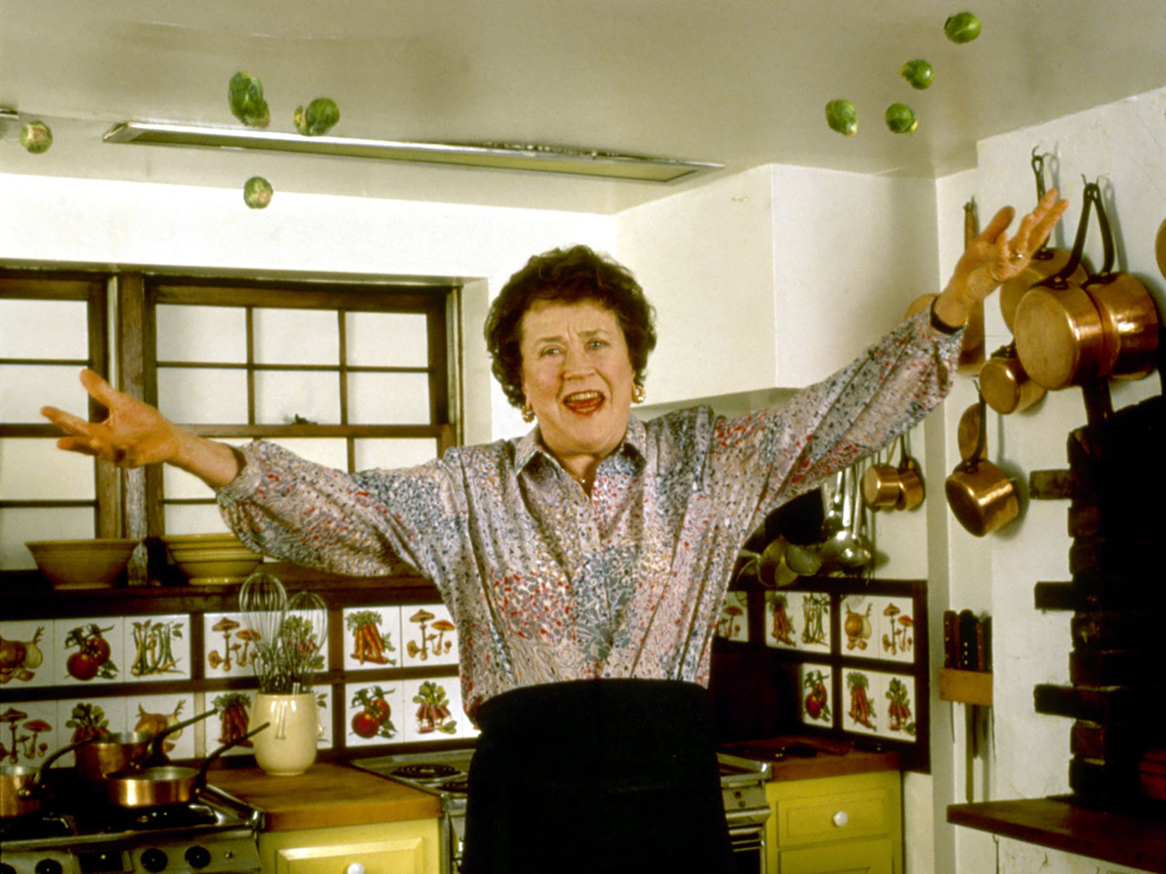 Chef Julia Child with her arms outstretched in her kitchen