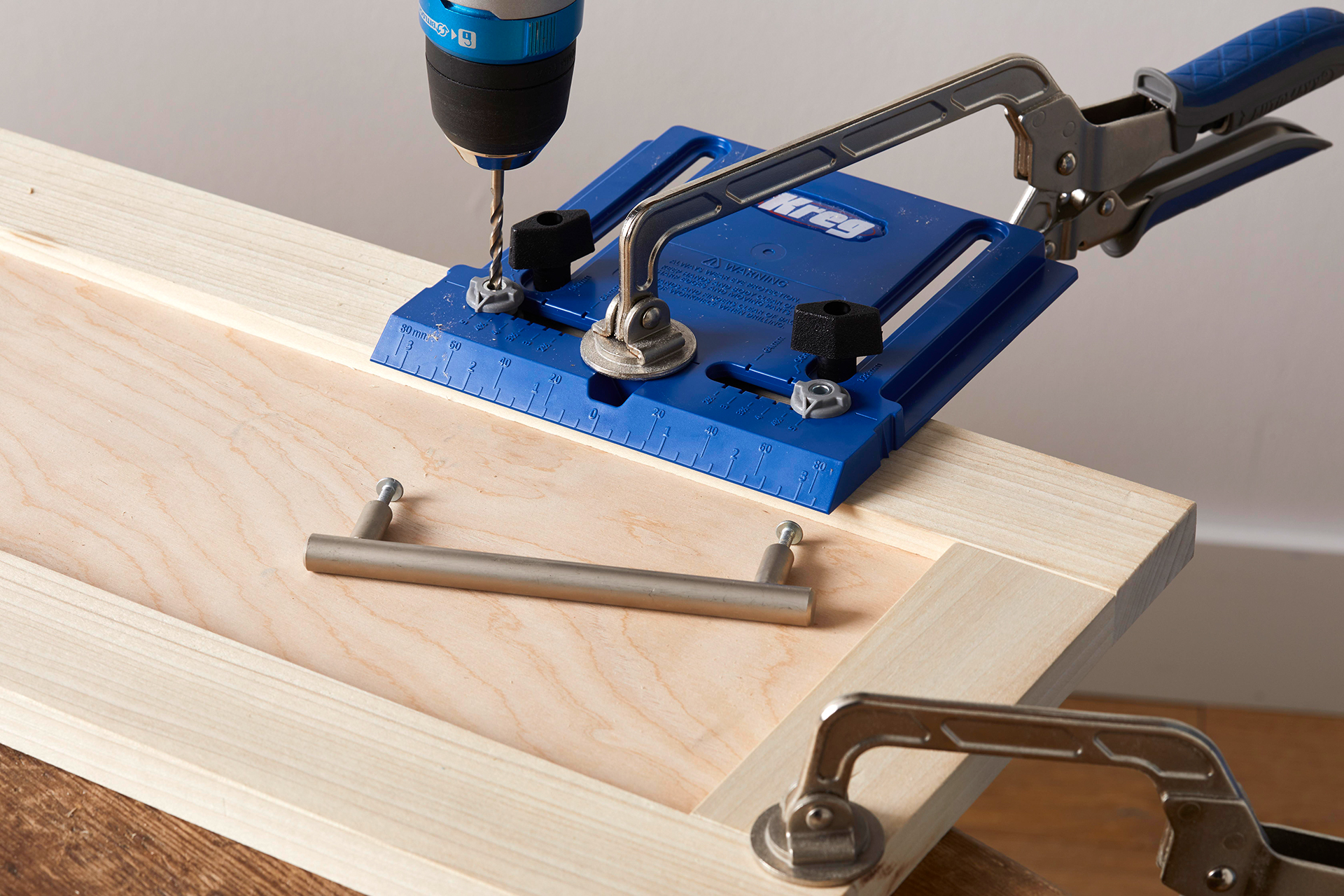 using tools to install handle for wood cabinets