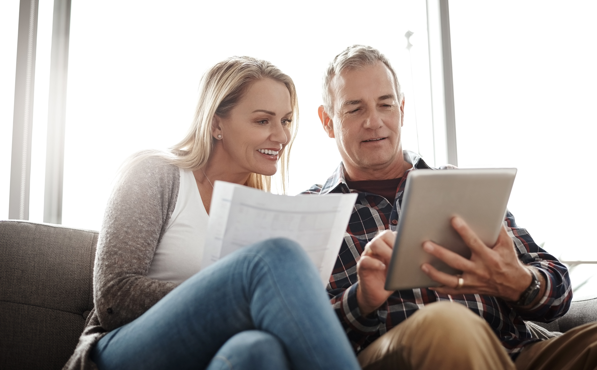Shot of mature couple using tablet to budget