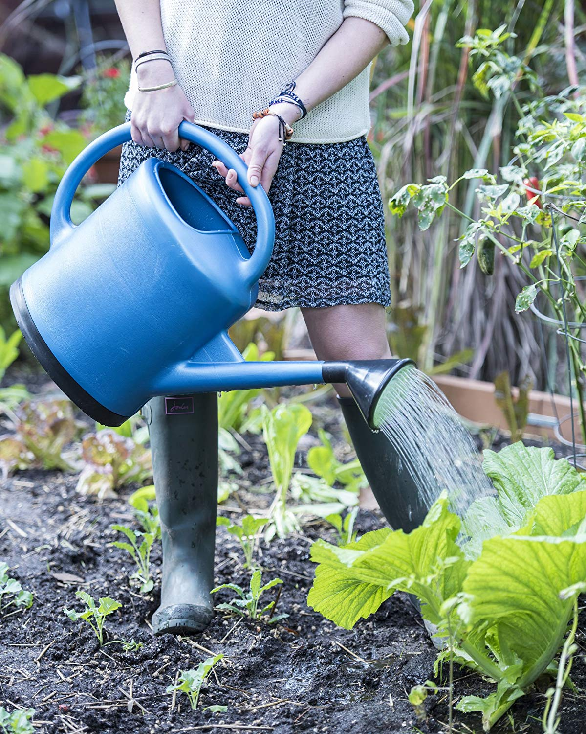 Woman in skirt and rain boots watering garden bed with oversize blue watering can