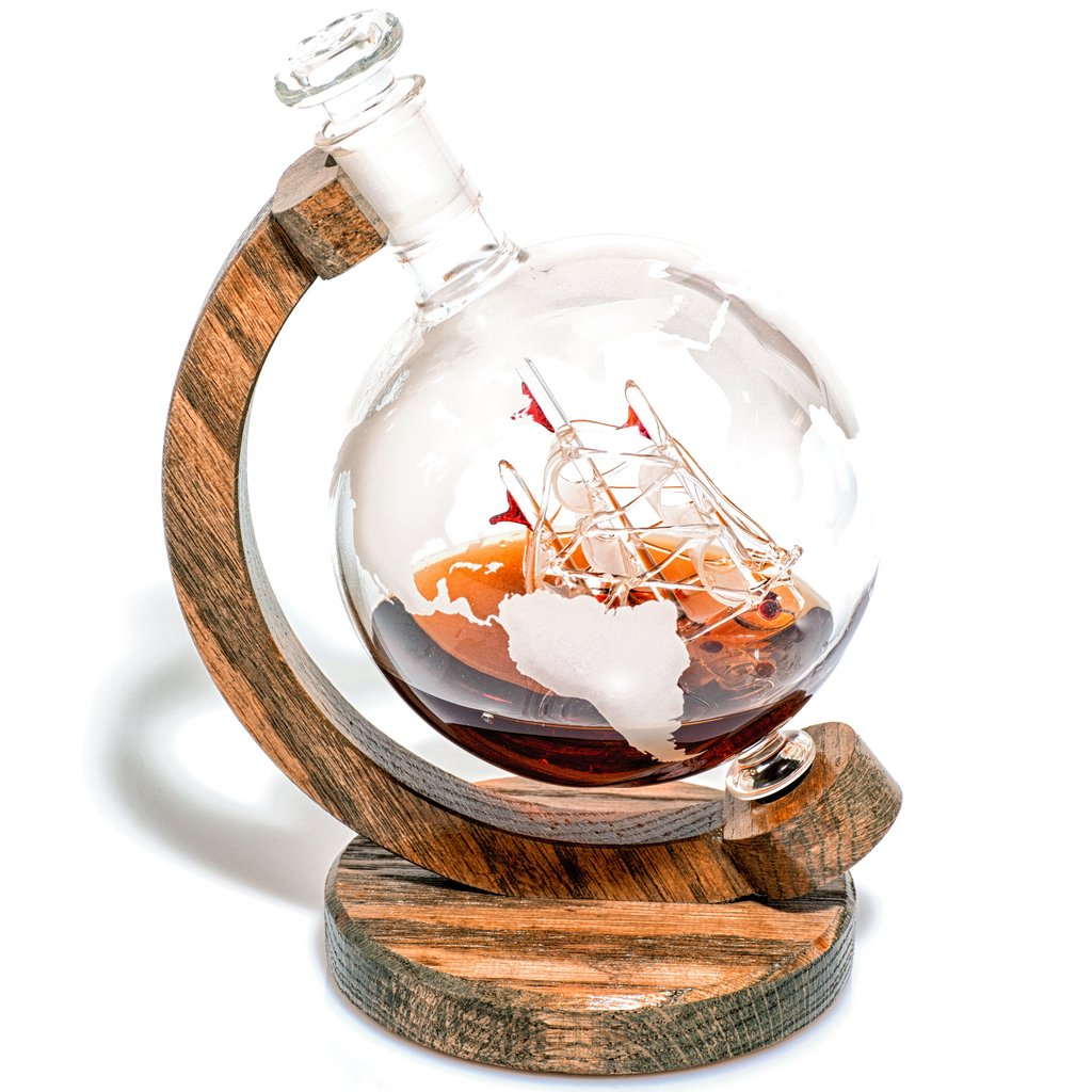 Blown glass decanter on wooden stand with etching of continents, glass ship inside partially submerged by brown liquor