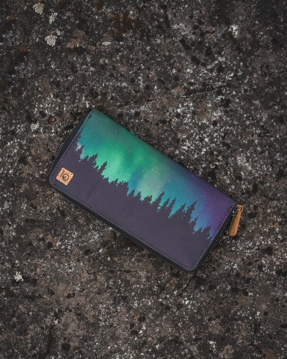 Leather zip wallet with northern lights and treeline silhouette design on outside