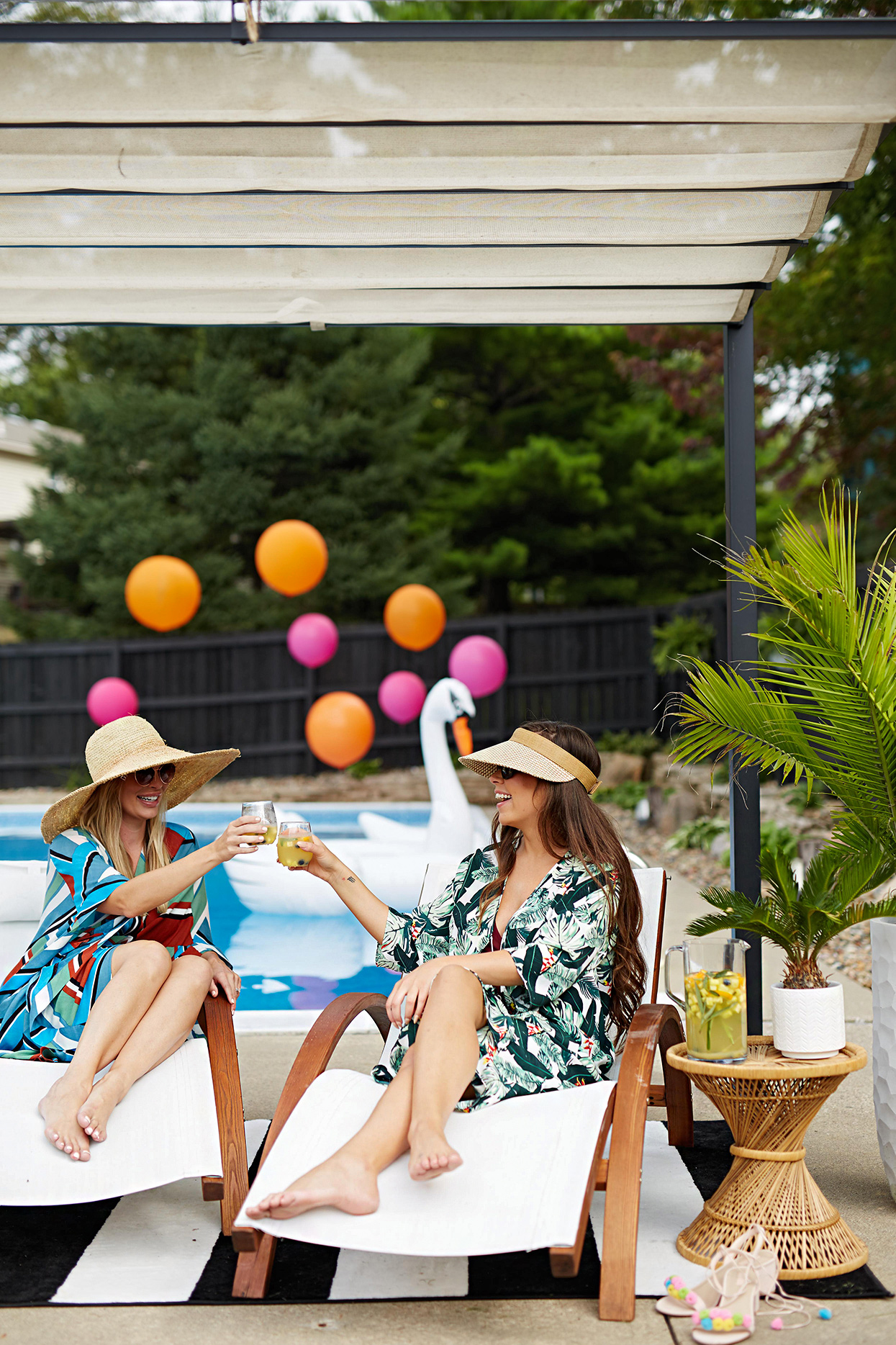 two women near pool with mixed drinks