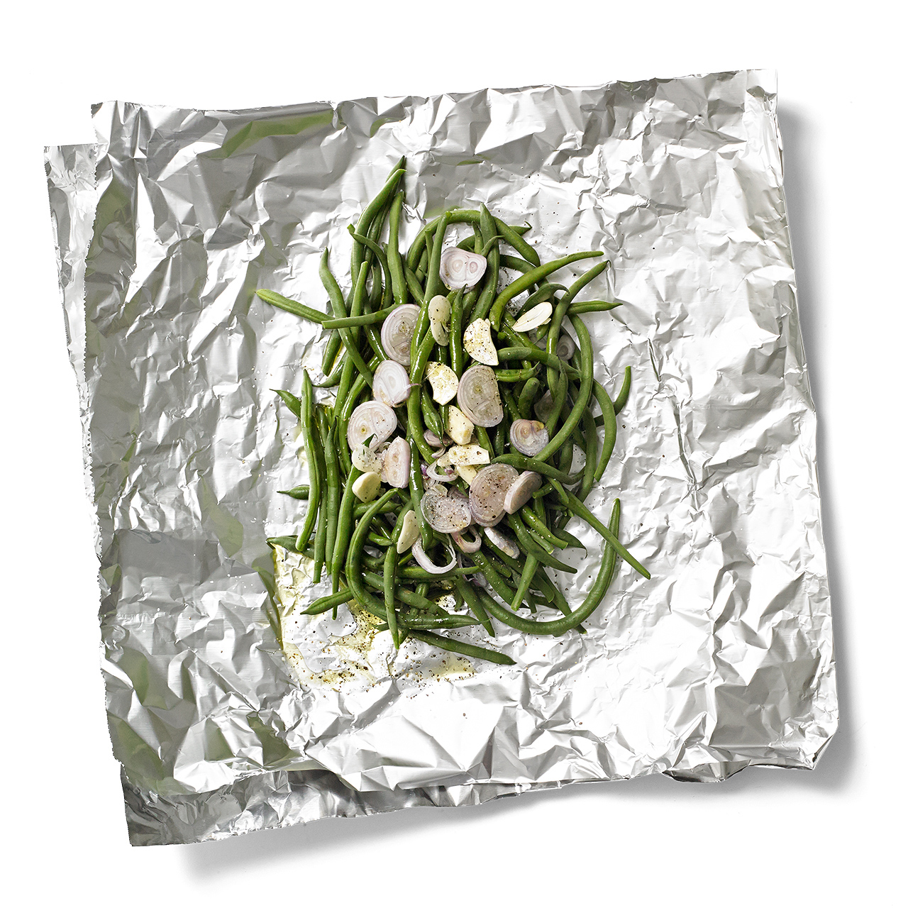 Green onions and slices of shallot on a large piece of foil to make a foil pack for grilling.