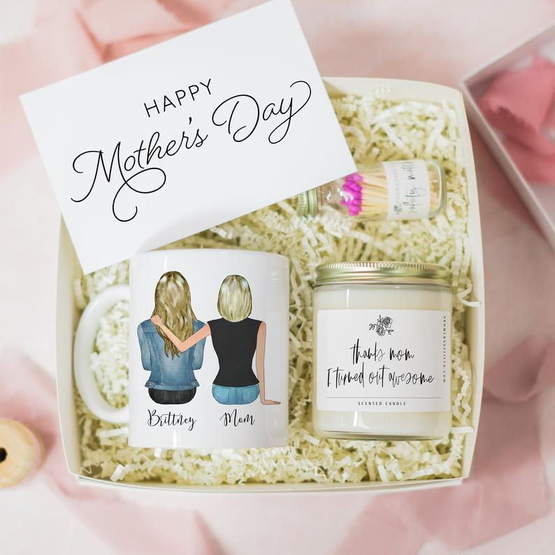 Box filled with white paper grass and a mug and candle