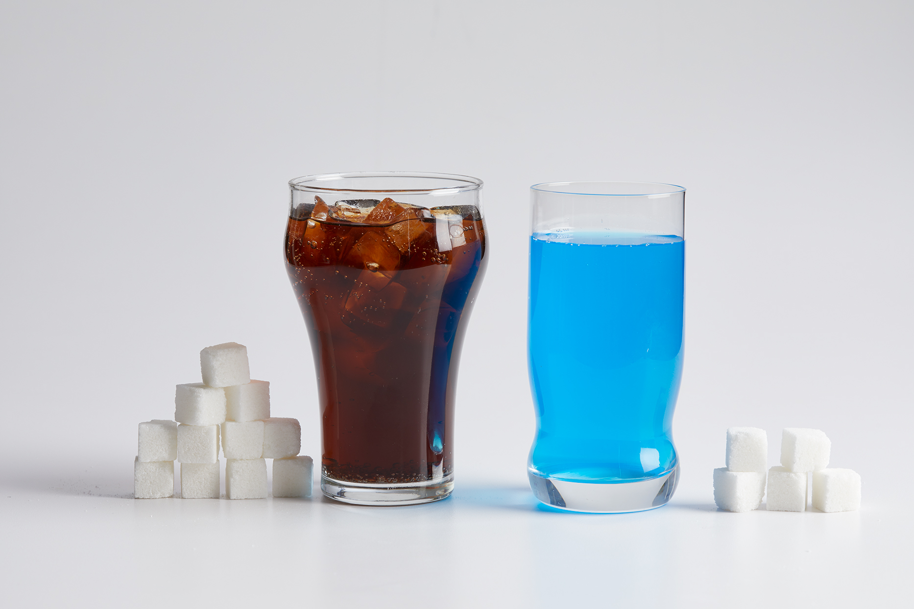 Soda and energy drink with piles of sugar cubes next to each glass on white background
