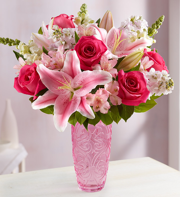 Pink vase with a bouquet of pink and white flowers and greenery