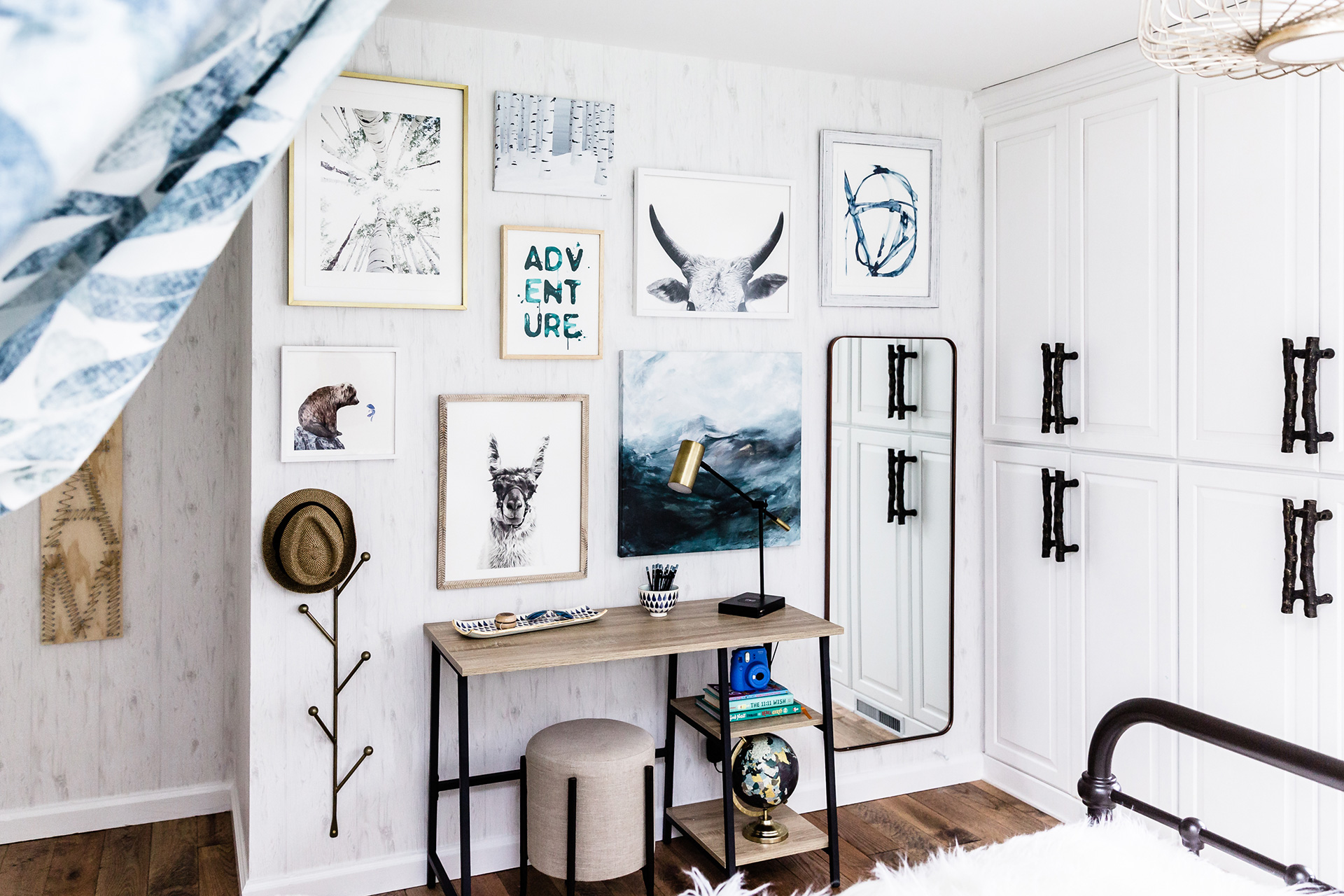 white bedroom with wall art and wood desk