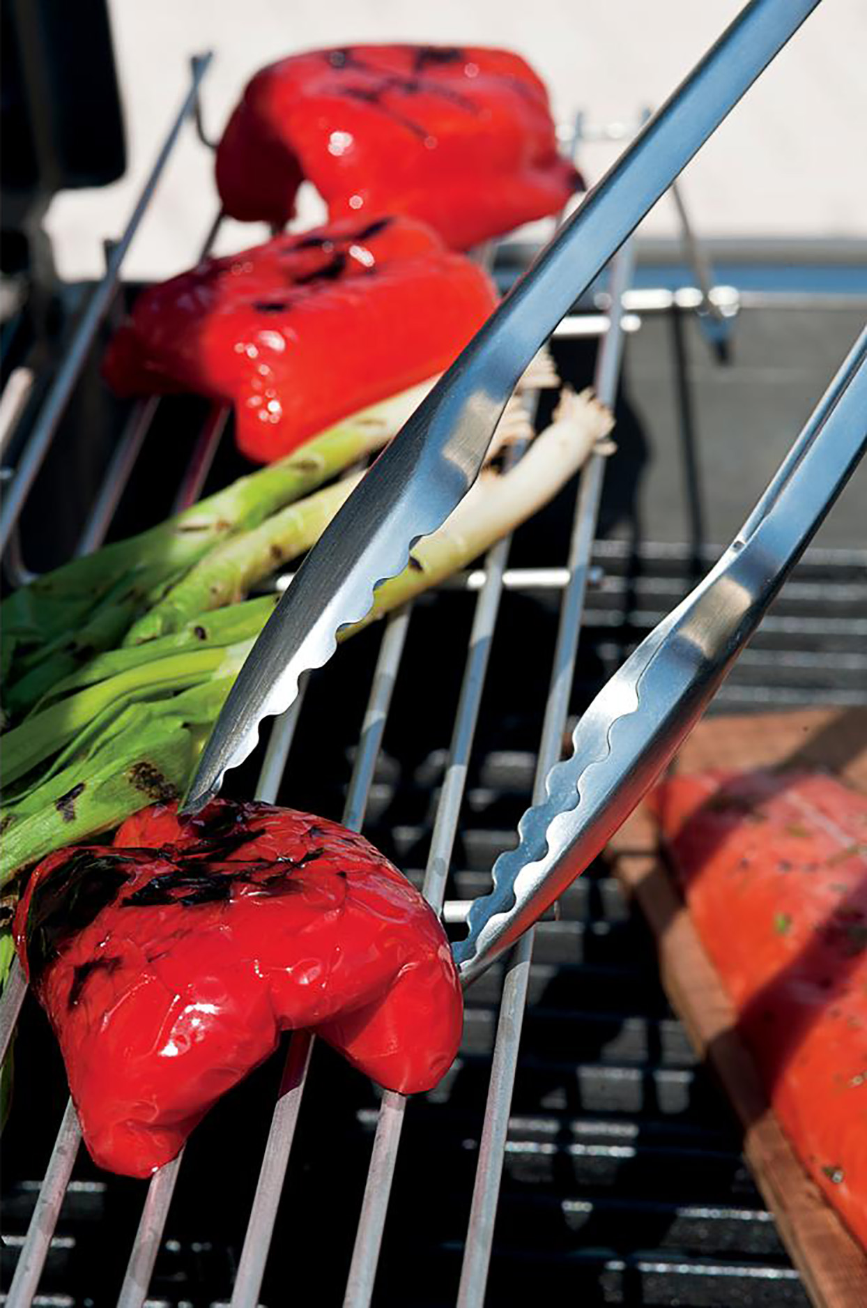 metal grill tongs turning a red pepper on a grill grate