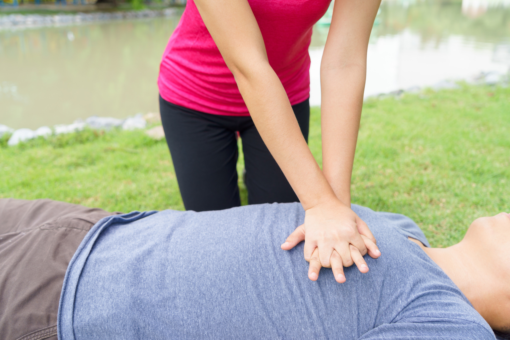 Woman giving cardiopulmonary resuscitation (CPR) to a man at public park (Woman giving cardiopulmonary resuscitation