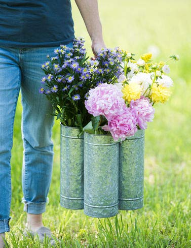 Woman holding galvanized flower caddy filled with flowers