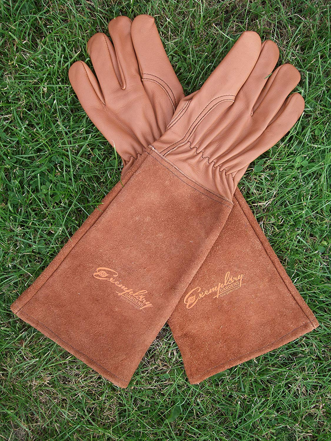 Brown leather rose pruning gloves laying in grass