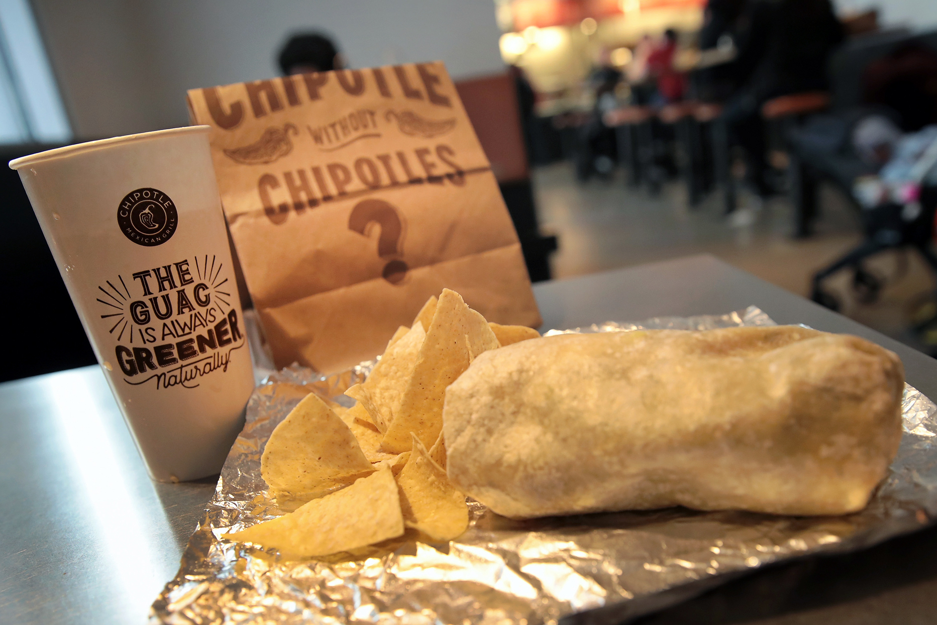 Chipotle meal of burrito and chips on foil in restaurant with drink cup and brown paper bag in background.