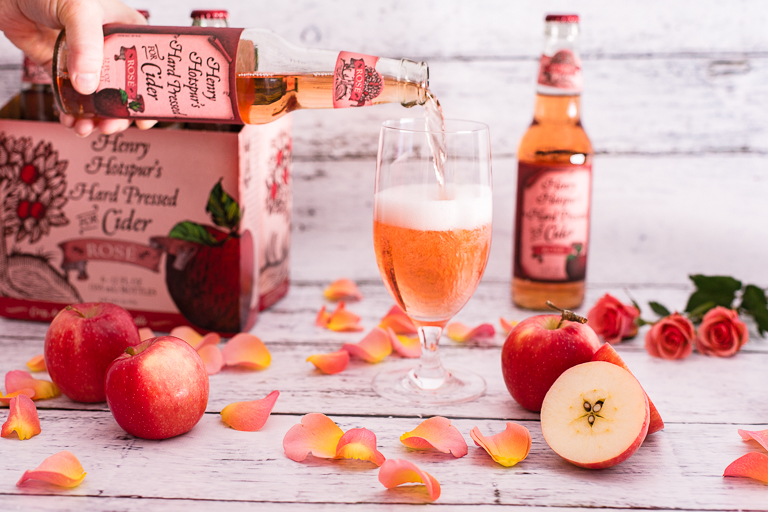 six pack of cider next to a glass of cider