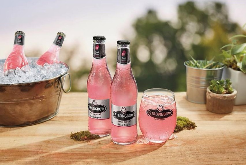 Two bottles of pink cider on a table next to a glass of pink cider