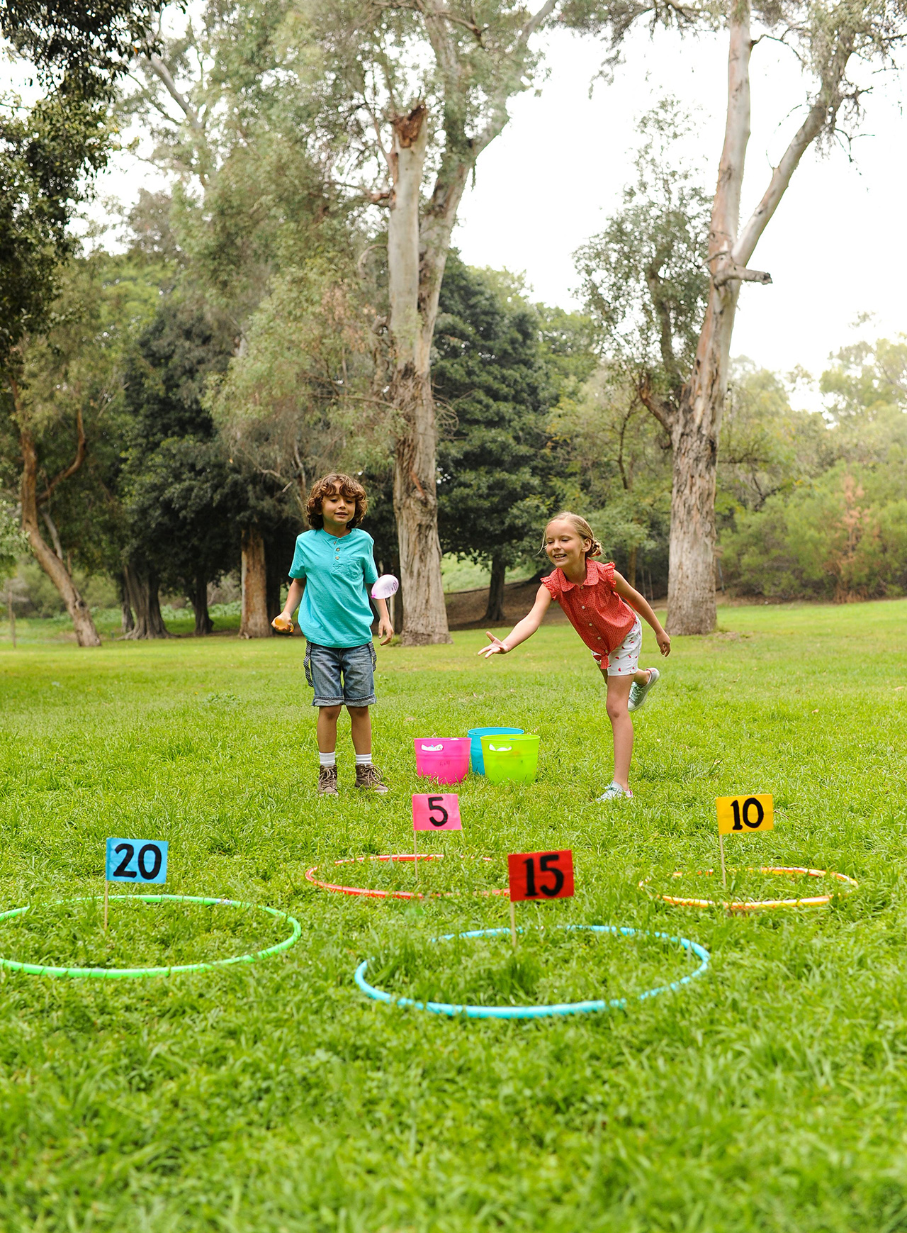 kids playing water balloon toss game with hula hoops