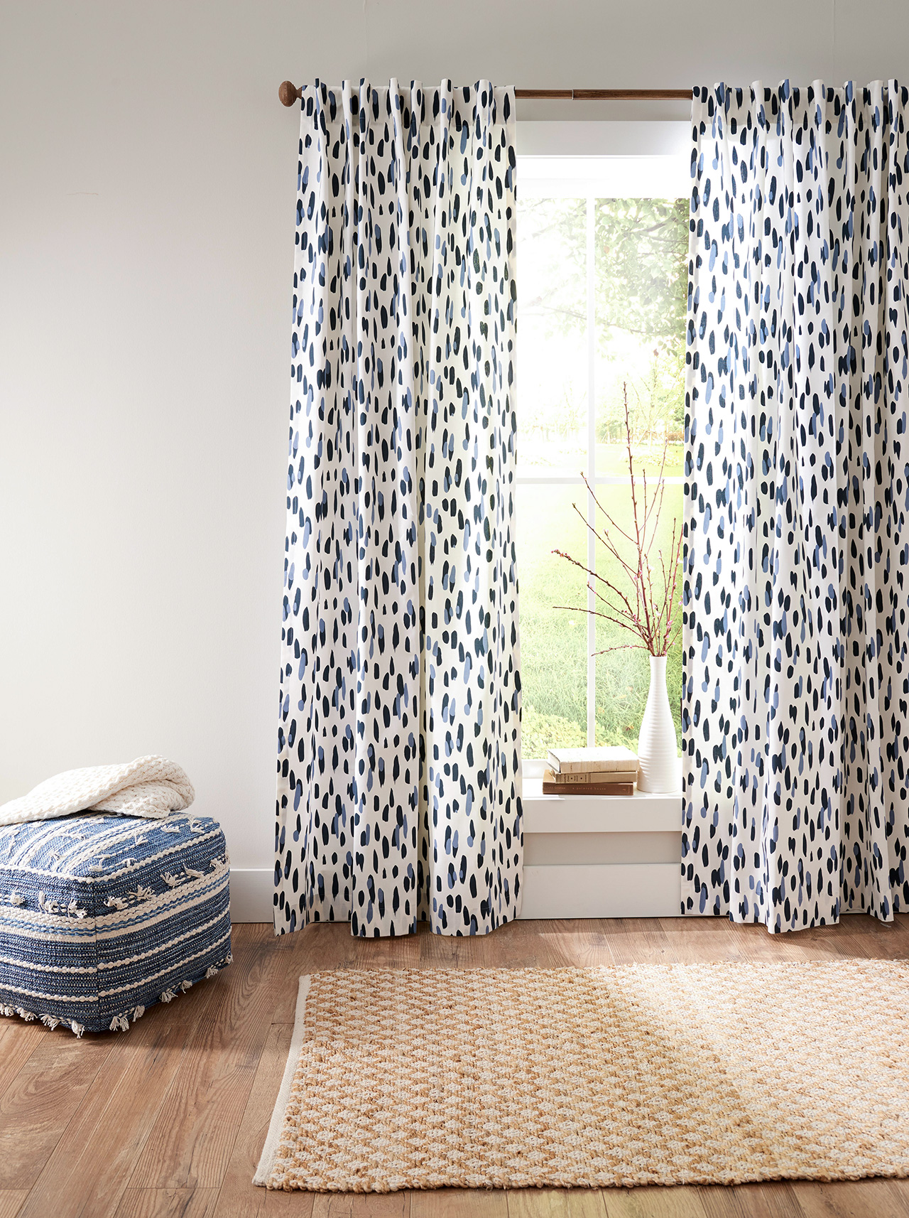 hung blue and white graphic curtains with blue ottoman