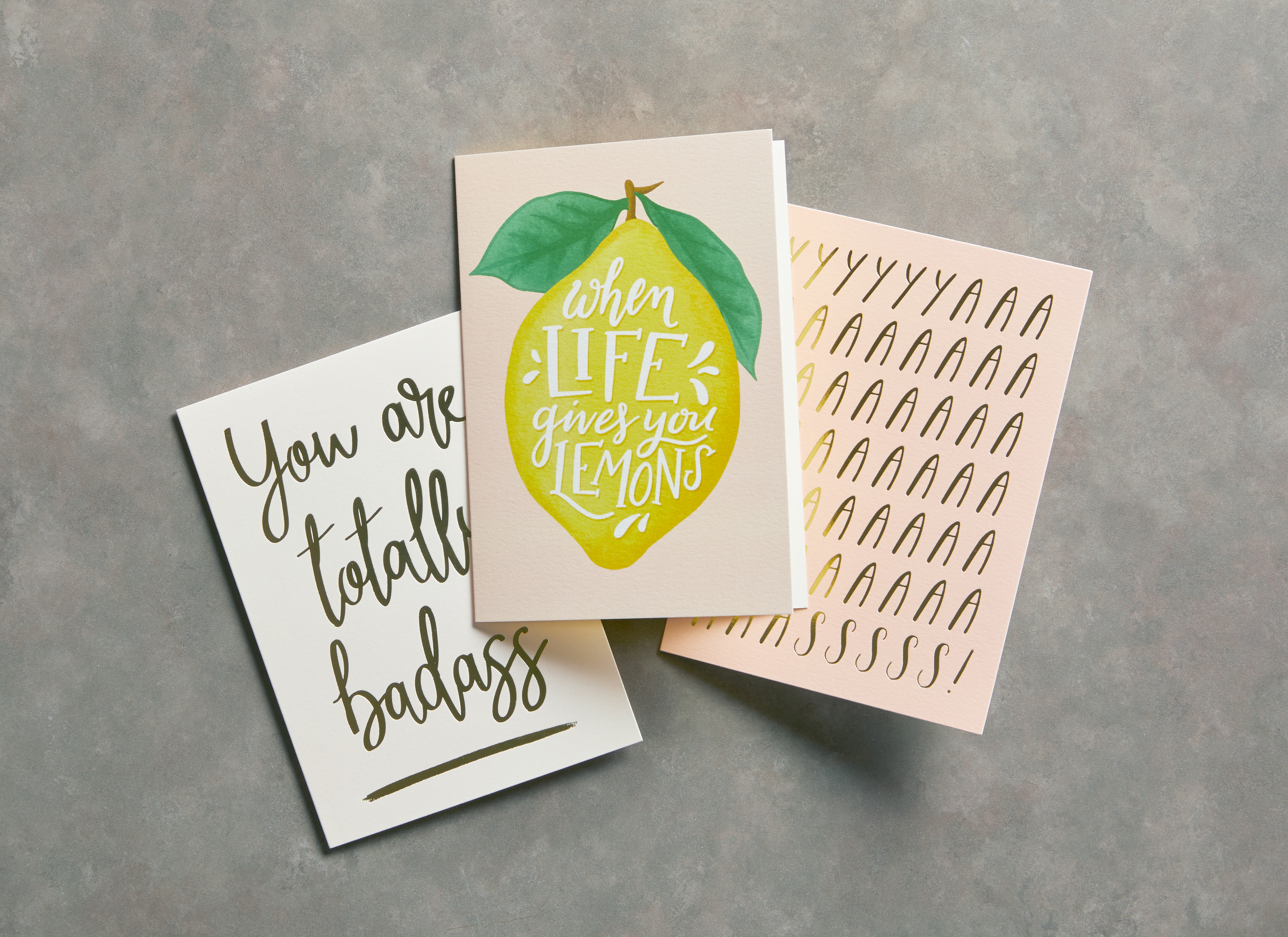 Three greeting cards on a gray surface